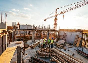 Conceito da indústria da construção - arquitetos e engenheiros debatendo o progresso do trabalho entre concreto, andaimes e guindastes